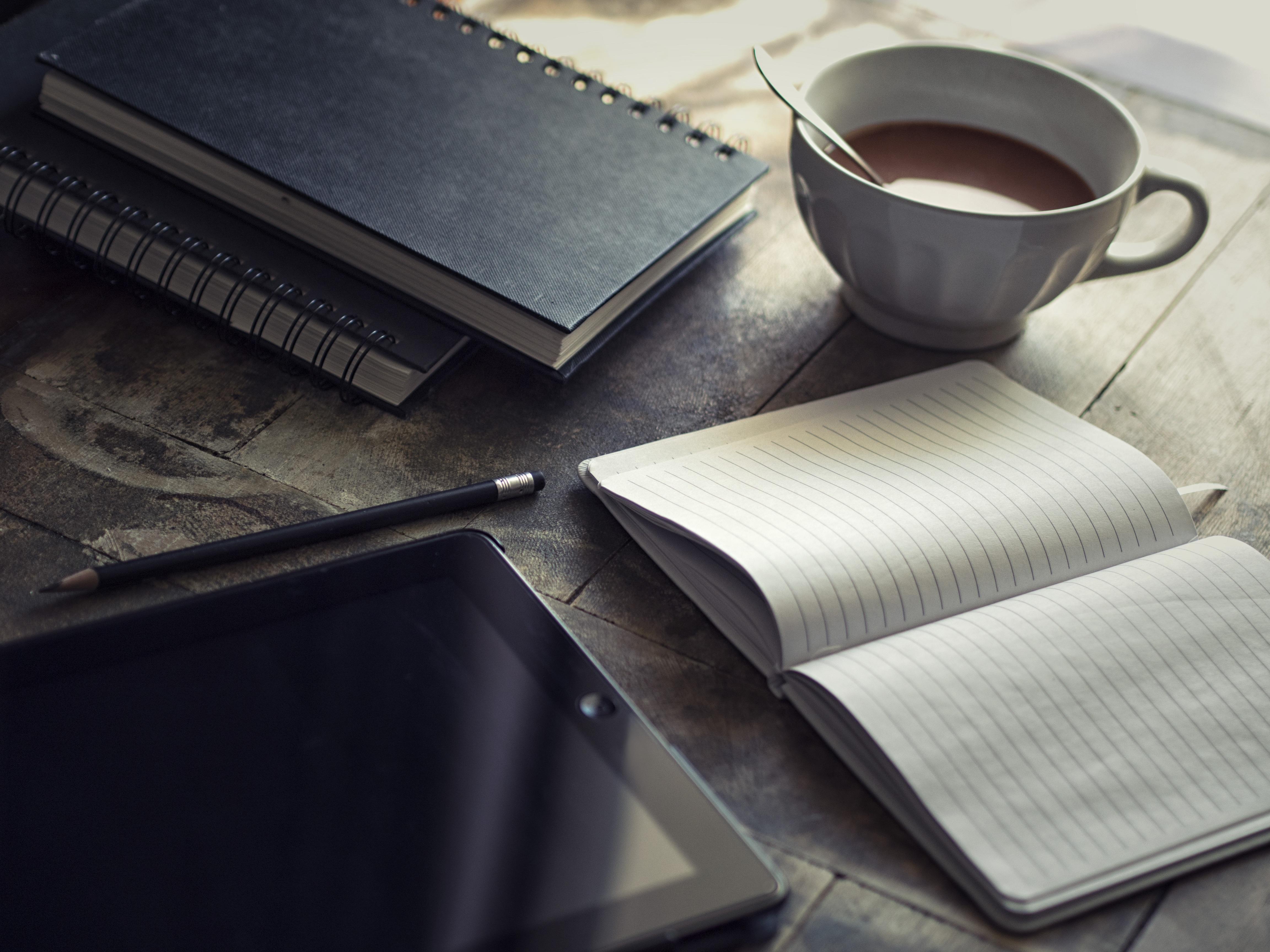 Coffee and note book on table